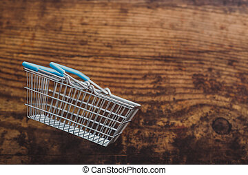 empty grocery store shopping basket on wooden surface