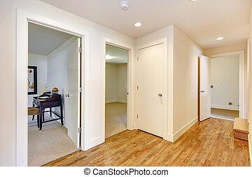 Empty hallway with hardwood floor, white walls. View of...