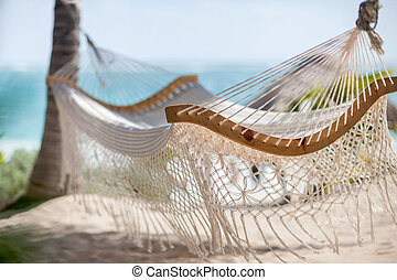 Empty hammock between palm trees on tropical beach