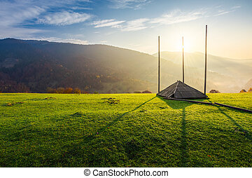 empty hay barrack on a grassy hill at sunrise. beautiful...