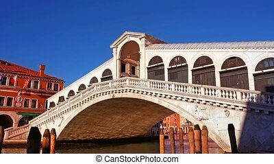 Wonderful empty historical Rialto bridge with arch passage in Venice city under clear blue sky during coronavirus quarantine