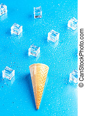 Empty ice cream cone and ice cubes on blue background