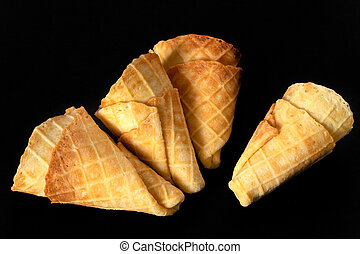 Collection of homemade empty ice cream cones isolated on black background.