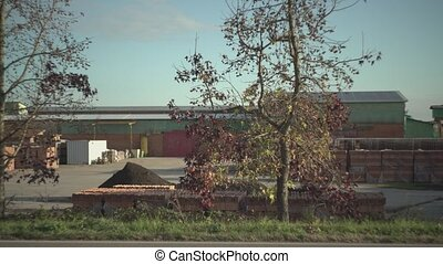Empty industrial site with tree in foreground