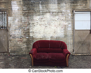 Empty interior with red sofa, blank concrete wall, minimalist living room design. Old cement wall background