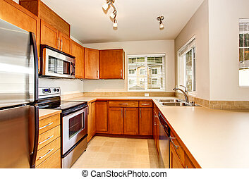 Empty kitchen room interior with wooden cabinets and tile floor.