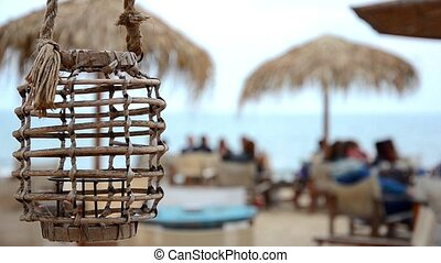 Empty lamp in a beach bar or cafe is swinging on a sea breeze on a Black sea seaside. Blurred sea. HD. 1920x1080