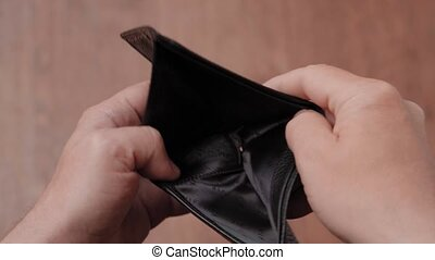Empty leather wallet in the hands of a man, close-up. Poverty concept