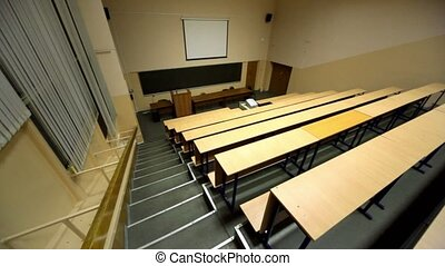 Empty lecture auditorium, white screen above blackboard,...