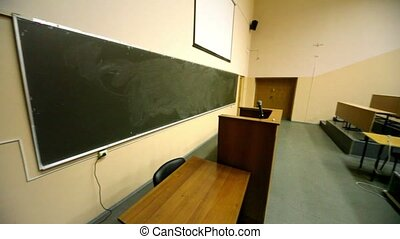 Empty lecture theater, white screen above blackboard,...