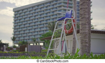 Empty lifeguard chair by the swimming pool in a big resort. The lifeguard is not on duty concept.