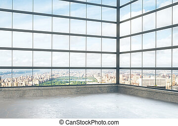 Empty loft style room with glassy windows and city view