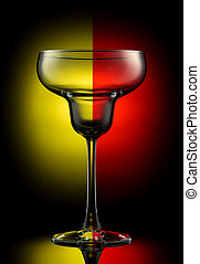 Empty margarita glass on a color background.