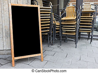 Empty menu board and stacked cafe chairs