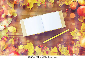 empty note book with pencil and autumn leaves
