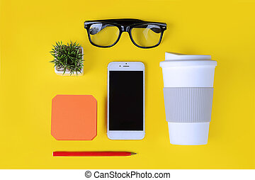 Empty note paper with plastic cup of coffee, pen, phone and glasses