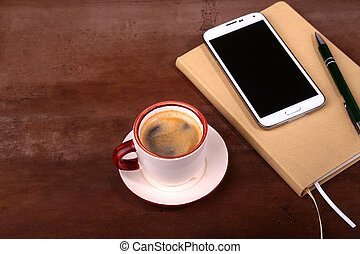 Empty notebook and ball pen with a cup of coffee, phone of the office desk. Business concept