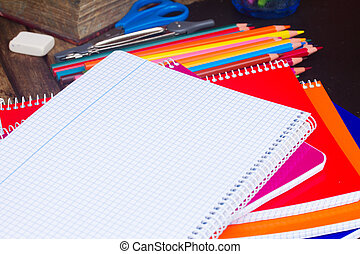 Empty notebook and set of colorful pencils on black board