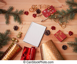 Empty notebook, fir branches, wrapping paper's rolls, gift box and christmas decorations on wooden background.