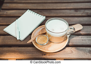 Empty notebook paper for text with white pen on wooden table at coffee shop.