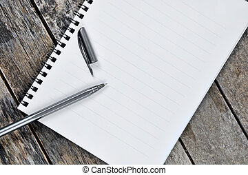 Empty notebook with pen on a wooden table