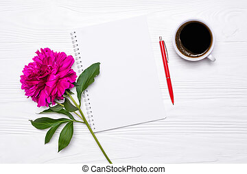 Empty notepad with place for text, pen, cup of coffee and peony flower on white