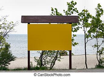 empty noticeboard, sea in background