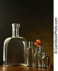 Empty old bottles, sepia tinted and flower, over vintage...