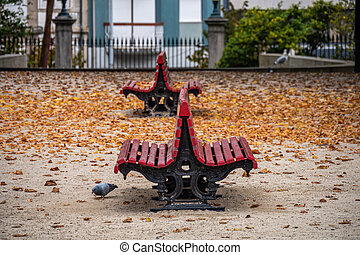 Empty old red benches in city autumn park with fallen leaves.