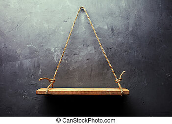 Empty old wood shelf hanging on rope on textured wall...