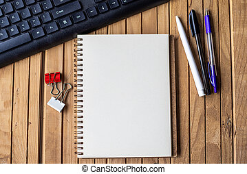 Empty Opened Clipped Journal Beside A Keyboard Pens On Top Of The Wooden Desk. Blank Open Notepad With Clip And Pencils Near Keypad Placed On Table.