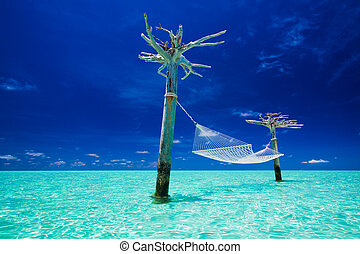 Empty over-water hammock in the middle of tropical lagoon