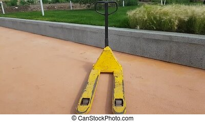 Empty pallet truck - Empty yellow pallet truck outdoors.