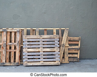 Empty pallets stacked against wall outside