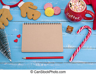 paper notebook and cup of hot chocolate with marshmallow