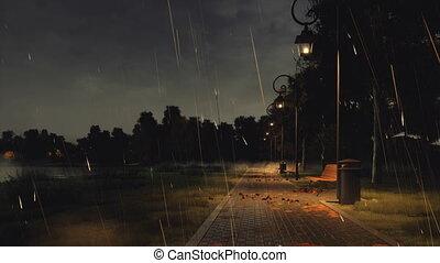 Empty park walkway at autumn night with heavy rain