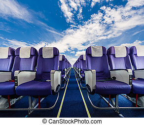 Empty passenger airplane seats with clouds sky