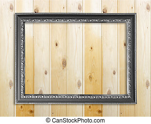 Empty picture frame on wooden wall.