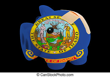 empty piggy rich bank in colors of flag of us state of idaho on black background