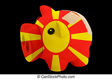 empty piggy rich bank in colors of national flag of macedonia on black background