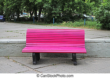 Empty pink wooden bench on the street