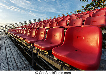 Empty plastic chairs at temporary grandstand stadium in...