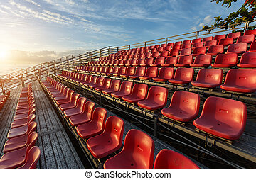 Empty plastic chairs at temporary grandstand stadium in ...