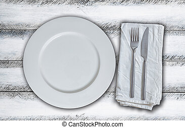 Empty plate and cutlery on white vintage wood