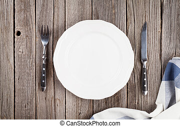 Empty plate and silverware on wooden table