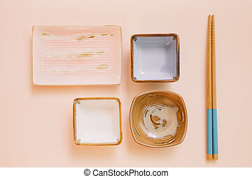 Empty plate and wooden chopsticks on pink background