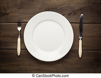 empty plate on a wooden table with fork and knife