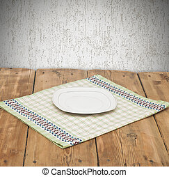 Empty plate on tablecloth on wooden table over grunge background