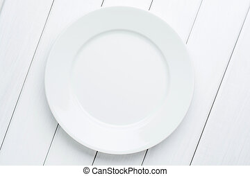 Empty plate on white planked wooden background. Top view with copy space
