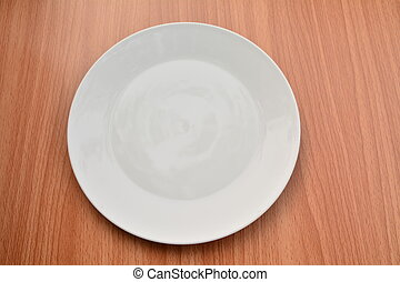 Empty plate on wood table background. View from above